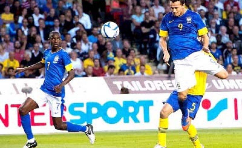 Leandro Damião (9) salta para marcar o primeiro gol do Brasil