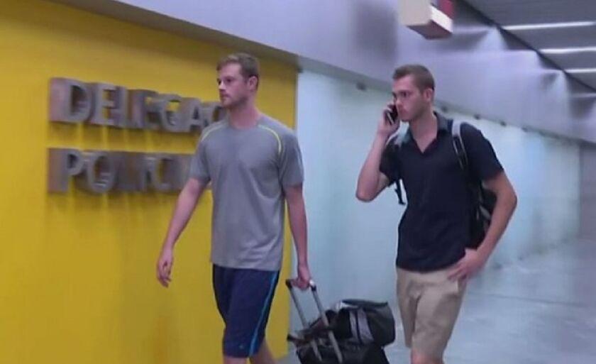 Nadadores americanos Jack Conger e Gunnar Bentz comparecem à delegacia depois de terem sido impedidos de embarcar em um voo para os Estados Unidos