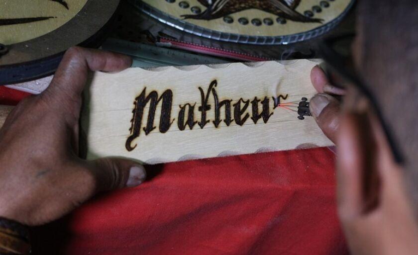 Artesão escreve com fogo nome em madeira para exposição artística
