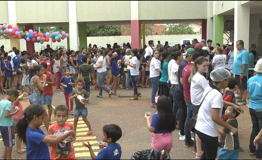 Crianças aguardam em fila, a distribuição de guloseimas e refrigerantes