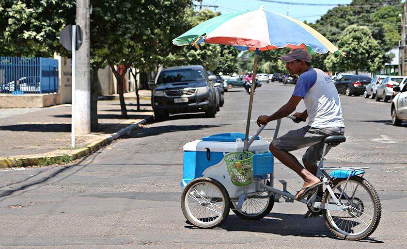 Vendedor de pícolés tenta se esconder do sol forte pelas ruas de Três Lagoas.
