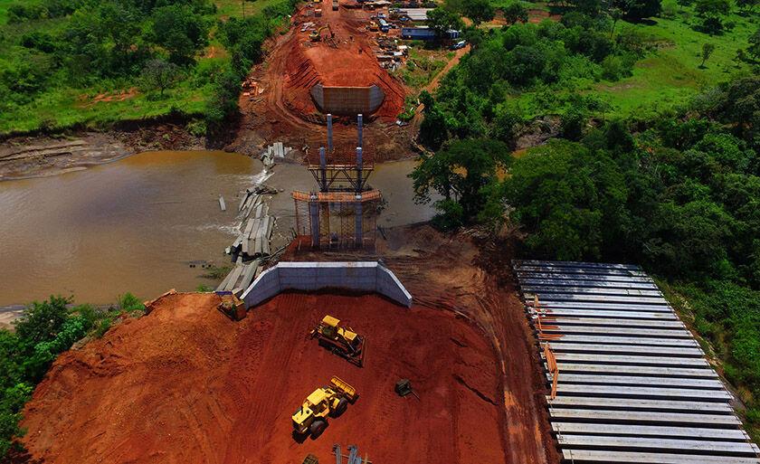Pilares da ponte estão em fase final de conclusão para fixação das vigas; máquinas preparam serviços de aterramento da rodovia
