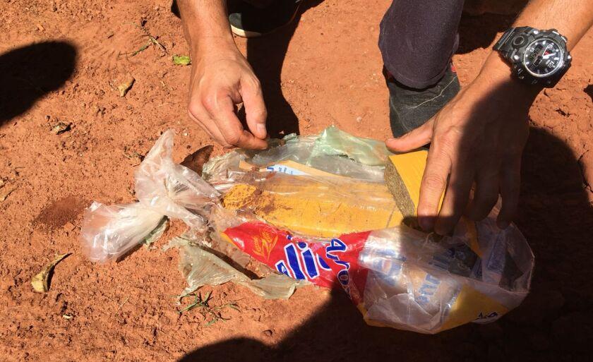 Policial abre pacote de drogas encontrado no quintal
