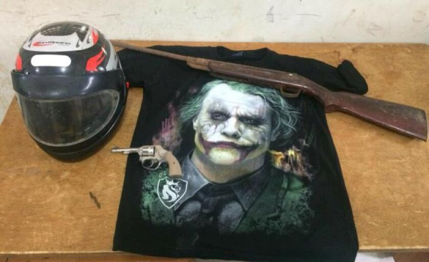 A polícia apreendeu um revólver ,uma espingarda e uma camiseta preta com desenho do coringa,