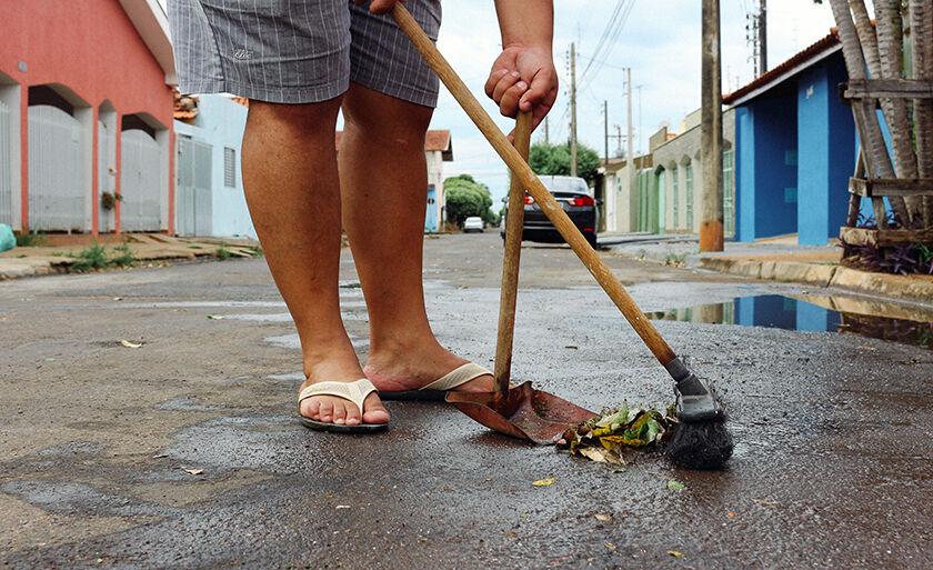 Depois da chuva e ventania desta madrugada, morador recolhe folhas da rua