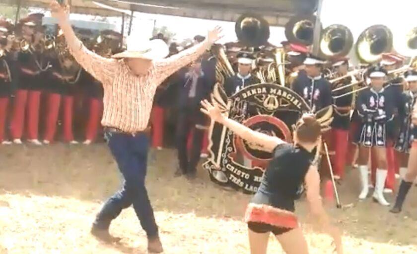 Guerreiro dança ao lado de menina, em festa pública
