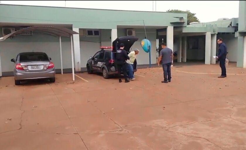 Walter Luís é retirado do carro da Polícia Civil, observado por investigadores, na quarta de manhã