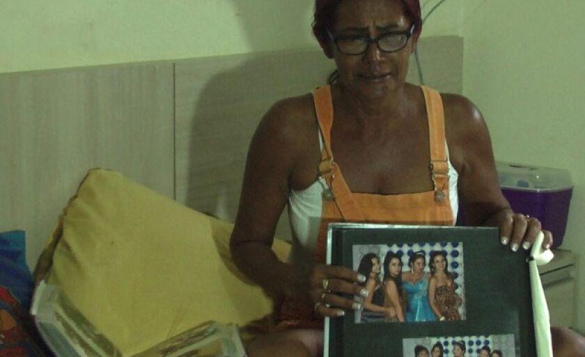 Maria Aparecida, mãe de Criskeila, segura álbum de fotos da festa de 15 anos da fillha, comemorado na Austrália